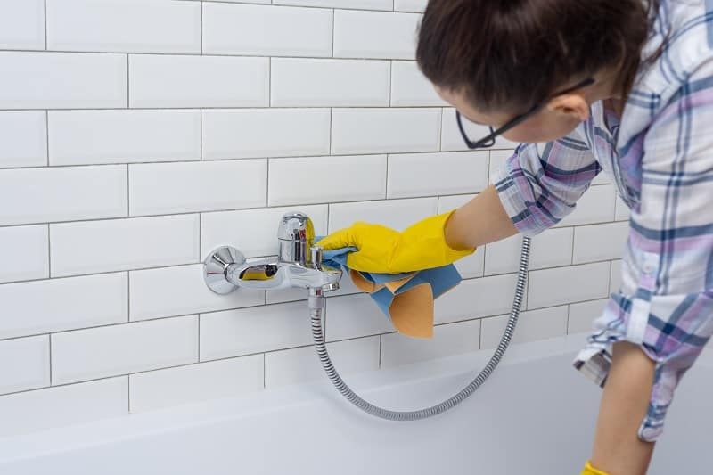 Woman cleaning shower attachment