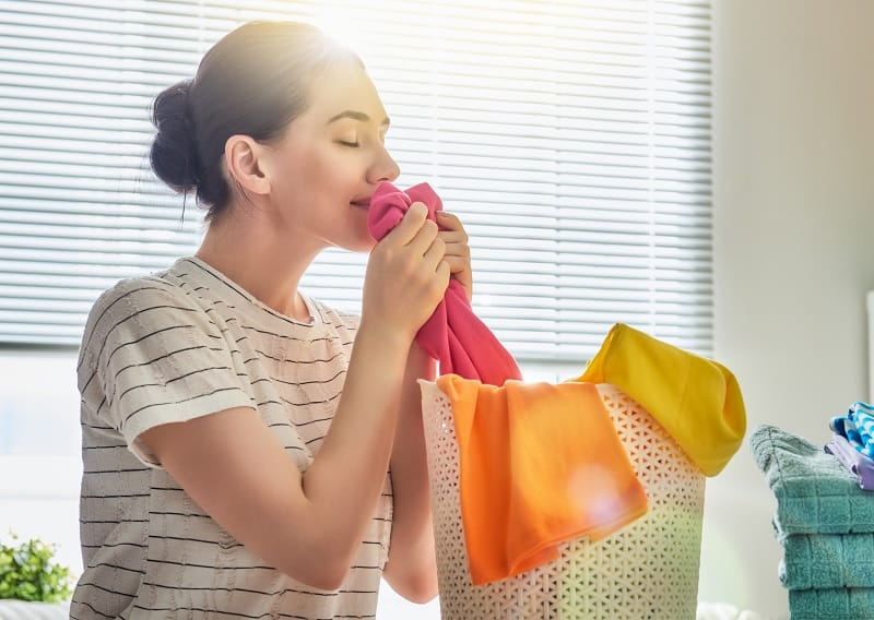 Woman smelling cloths while doing laundry