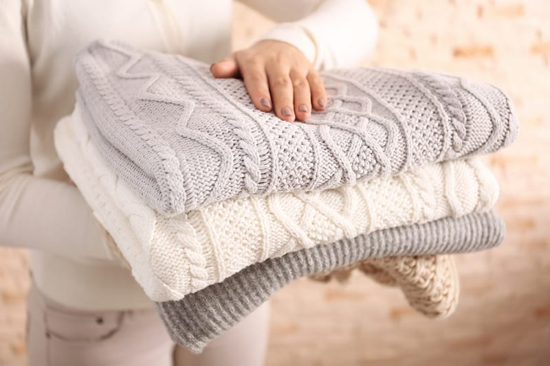 Woman holding folded woolen jumpers