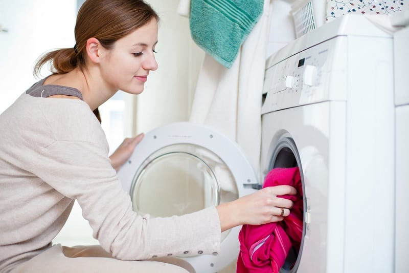 Woman washing colourful clothes