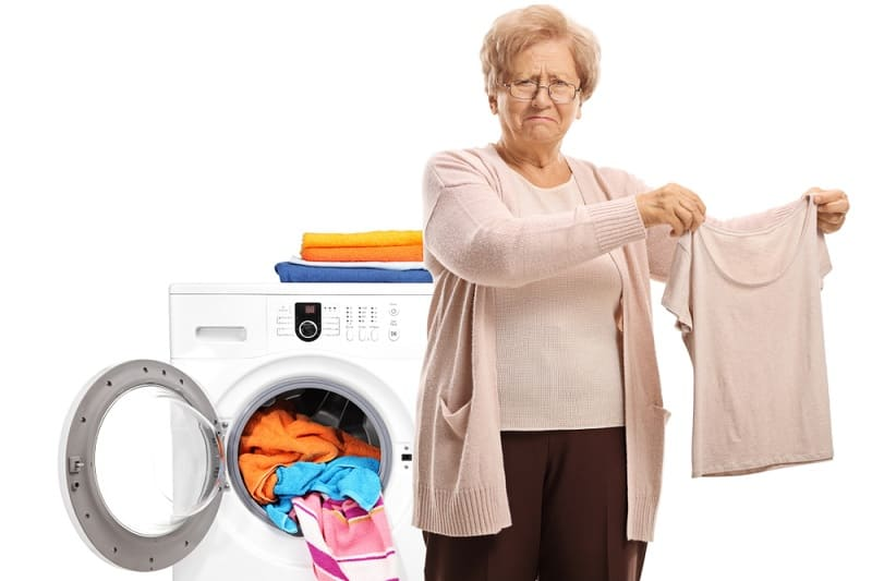 Upset woman holding blouse shrunk by washing machine