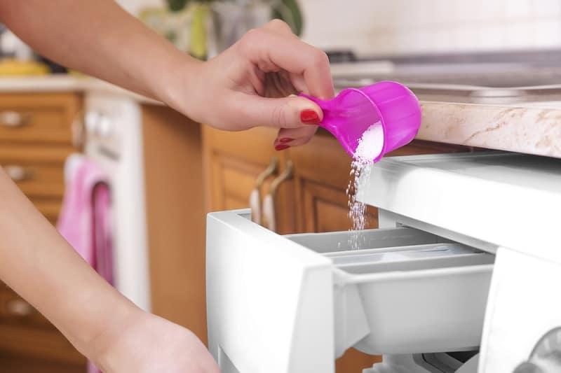 Woman putting washing powder in washing machine
