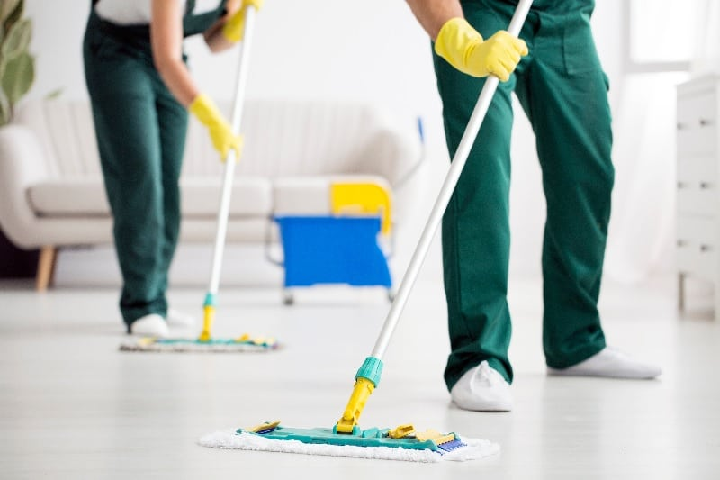 Professional cleaners mopping floor in living room