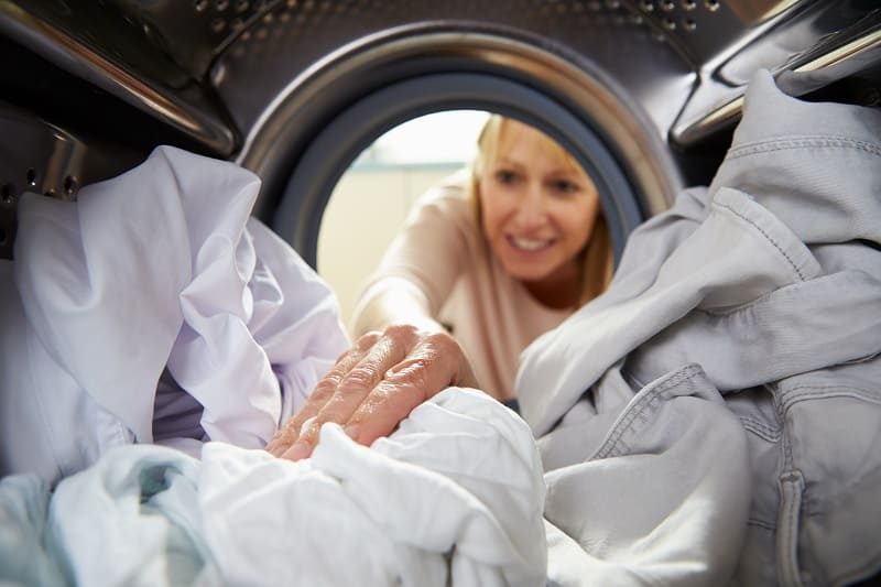 Woman checking clothes inside a tumble dryer drum
