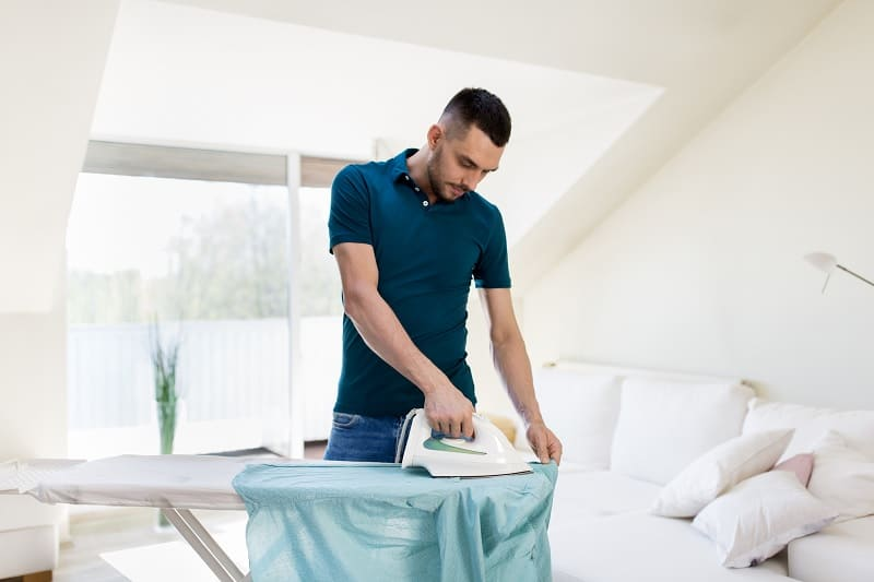 Man ironing shirt on an ironing board