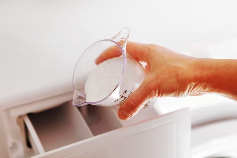 Woman's hand pouring washing powder into washing machine drawer