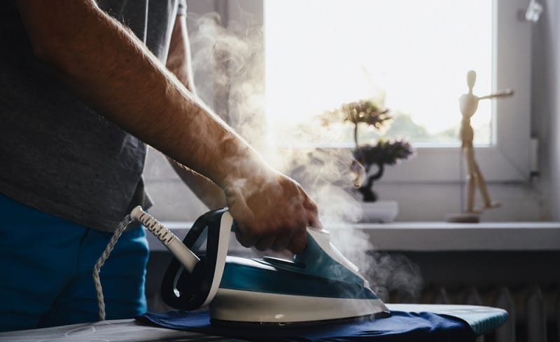 Man using a steam iron to iron clothes