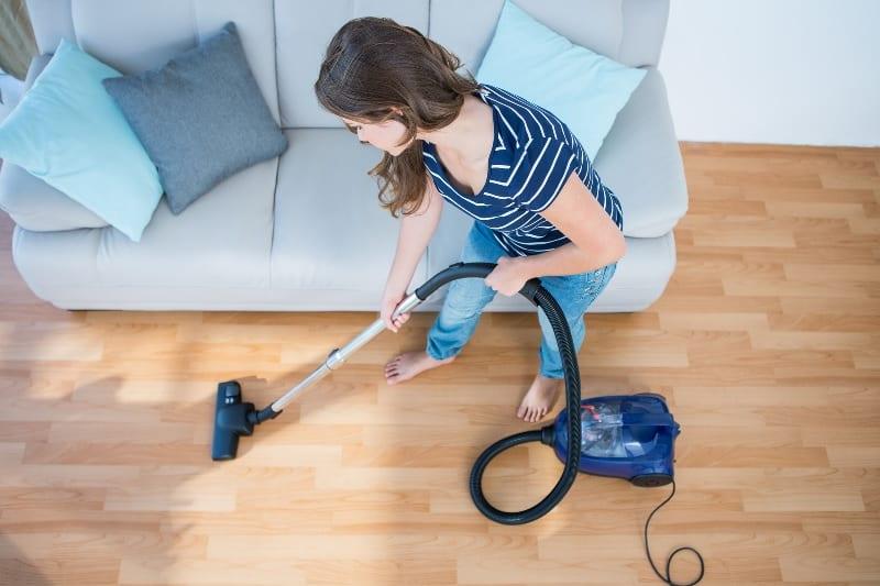 Woman vacuuming wood floor