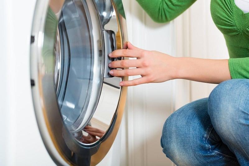 Hand on washing machine door