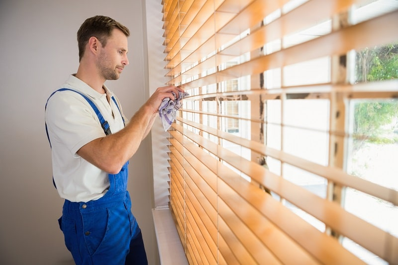 man cleaning window blind panels