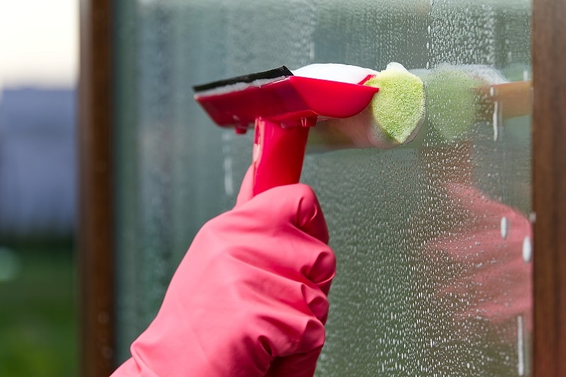 cleaning the window with squeegee