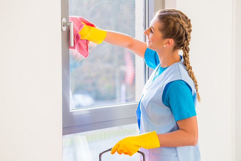 woman cleaning window with cloth