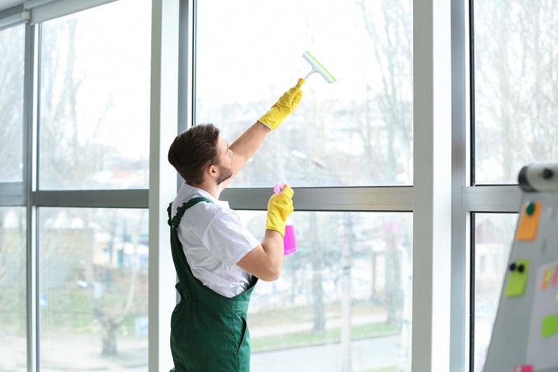 man cleaning big windows