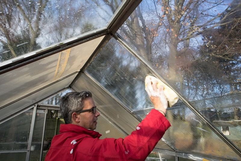 man cleaning conservatory windows