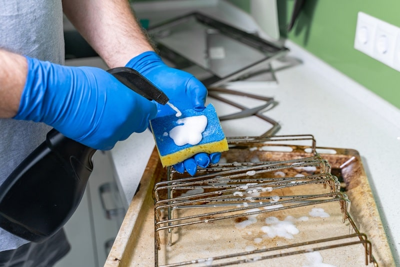 man cleaning dirty oven grills and trays